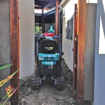 Excavator negotiating narrow entry walls